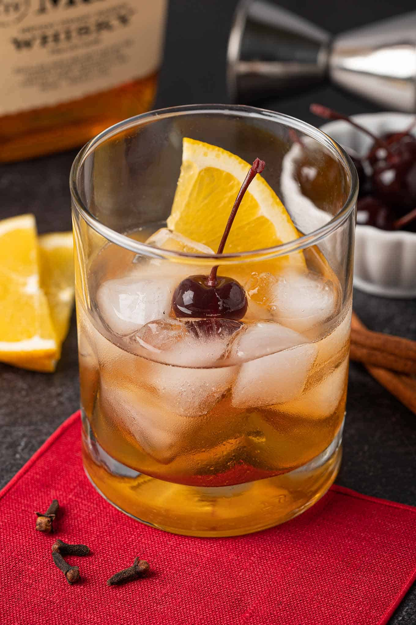 Old Fashioned cocktail garnished with an orange slice and a cherry, bourbon bottle, orange slices and cherries in the background