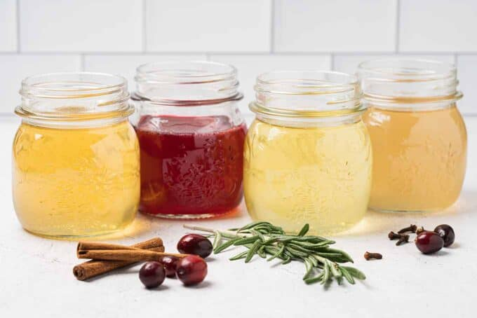 Four jars of spiced simple syrup, orange, cranberry, rosemary, and ginger spice.