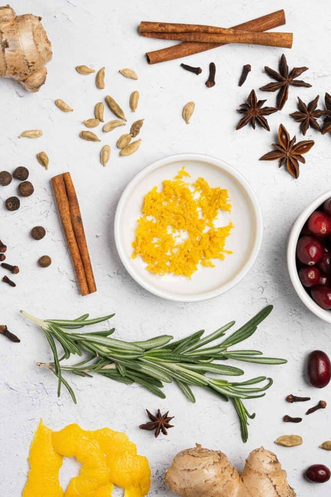 Spiced simple syrup ingredients on a board: ginger, cranberries, rosemary, orange zest, orange peel, cinnamon sticks, cloves, allspice, cardamom, and star anise