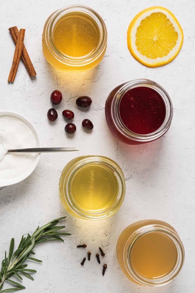 Top view of spiced orange, spiced cranberry, rosemary and winter spice syrups in jars along with a few of the ingredients for decoration