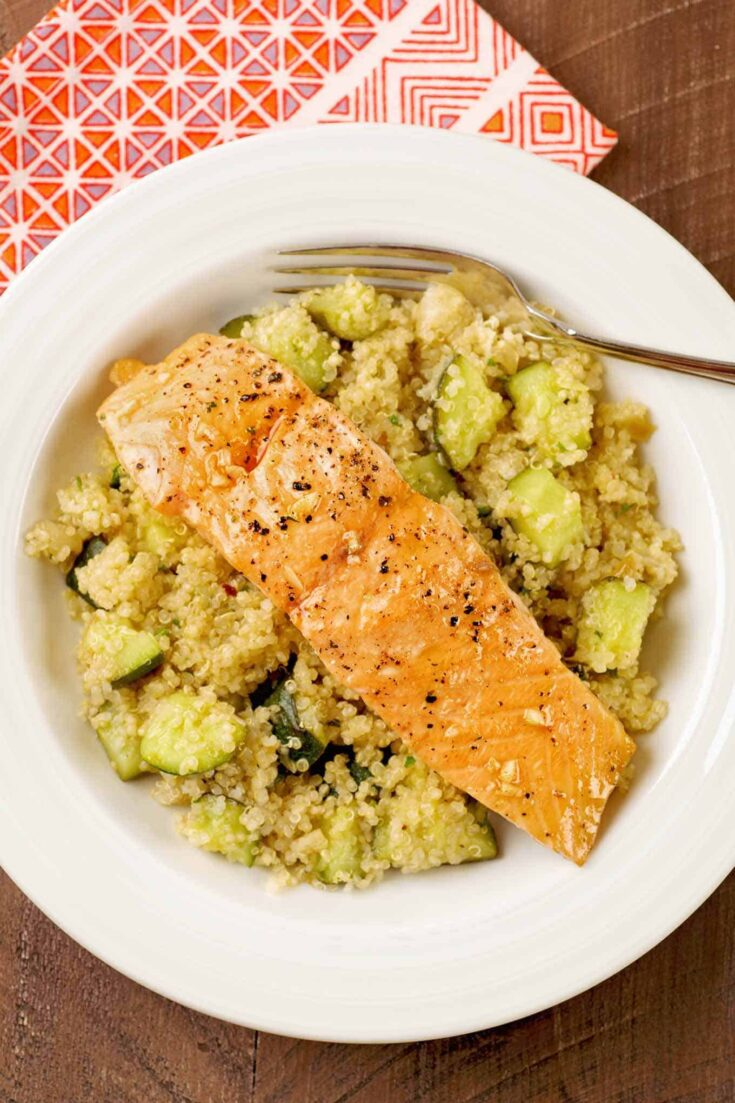Served on a bed of quinoa and roasted zucchini, these honey-garlic glazed salmon fillets make a fast and healthy one-dish dinner. #salmon #quinoa #zucchini