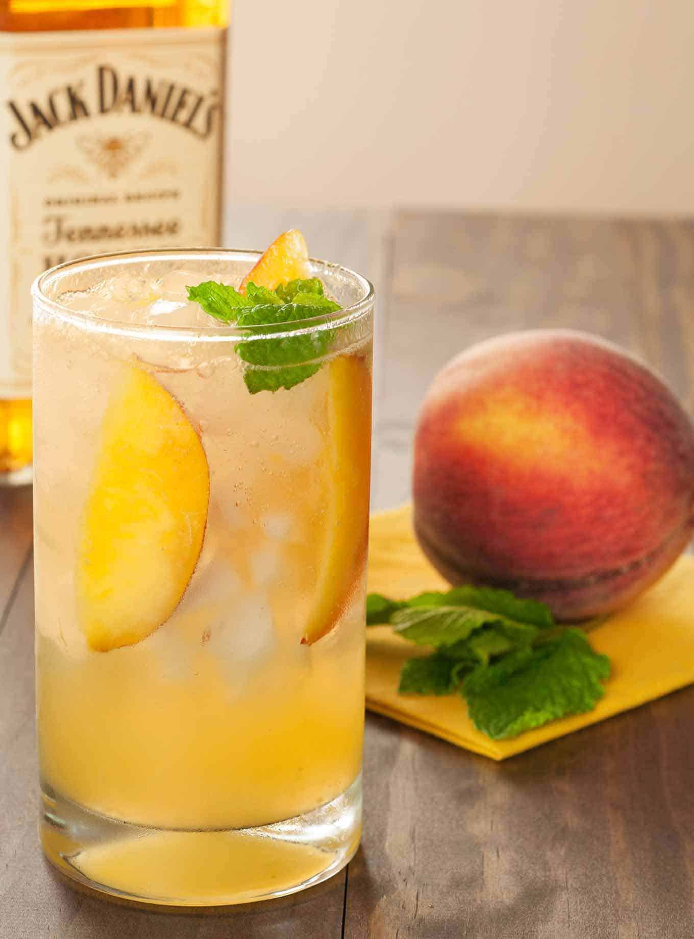 Cocktail garnished with peach slices and a sprig of mint with a whole peach and Jack Daniel's bottle in the background.