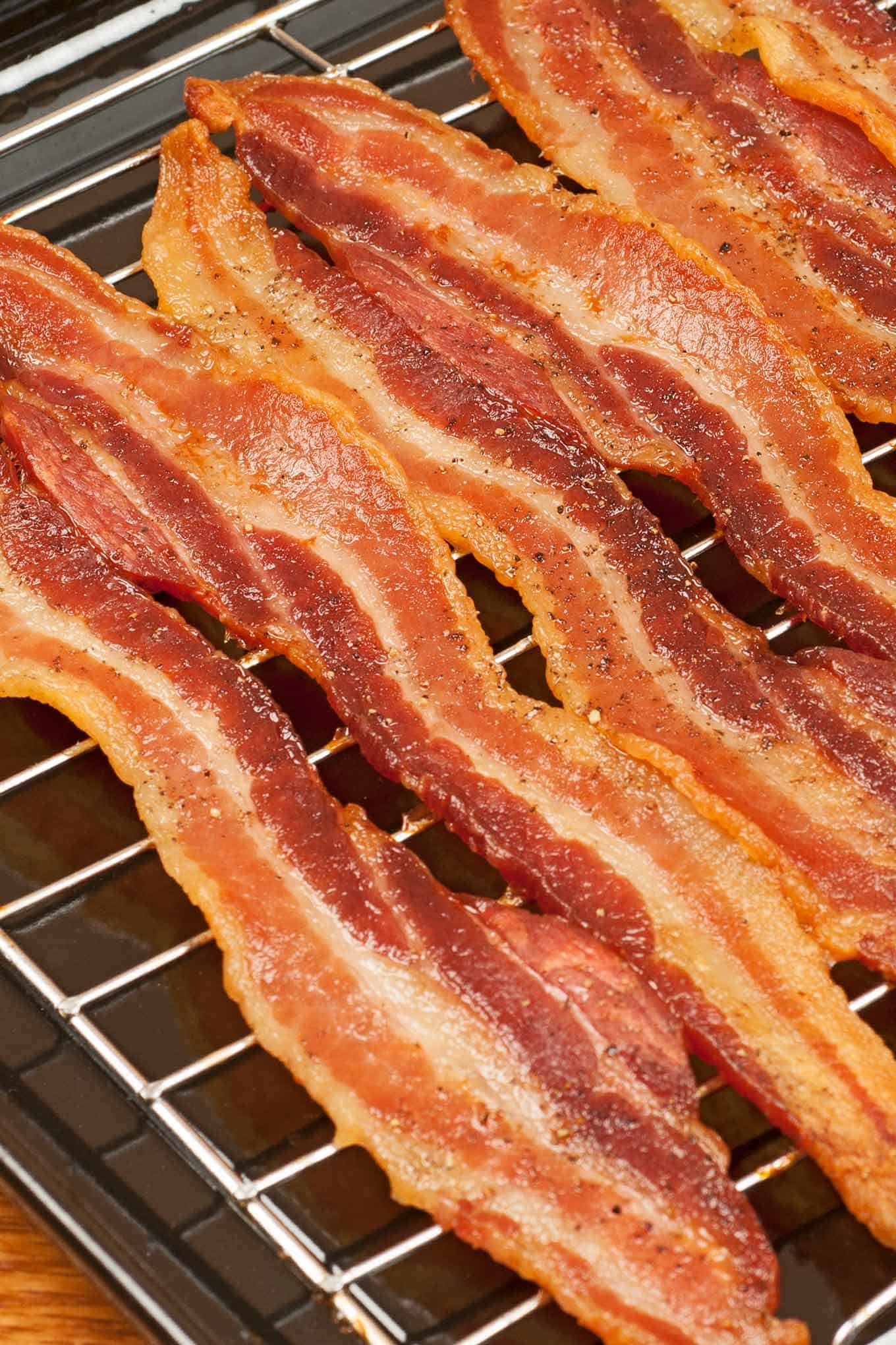 Crispy strips of baked bacon lined up on a rack inside a sheet pan.
