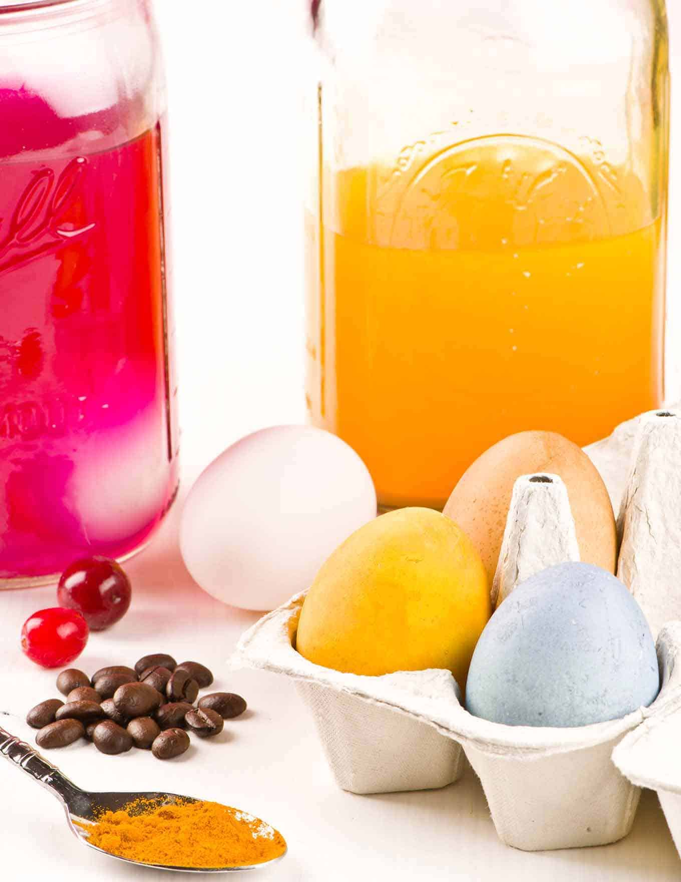 Naturally dyed eggs in an open carton with glass jars of yellow and red dye in the background.