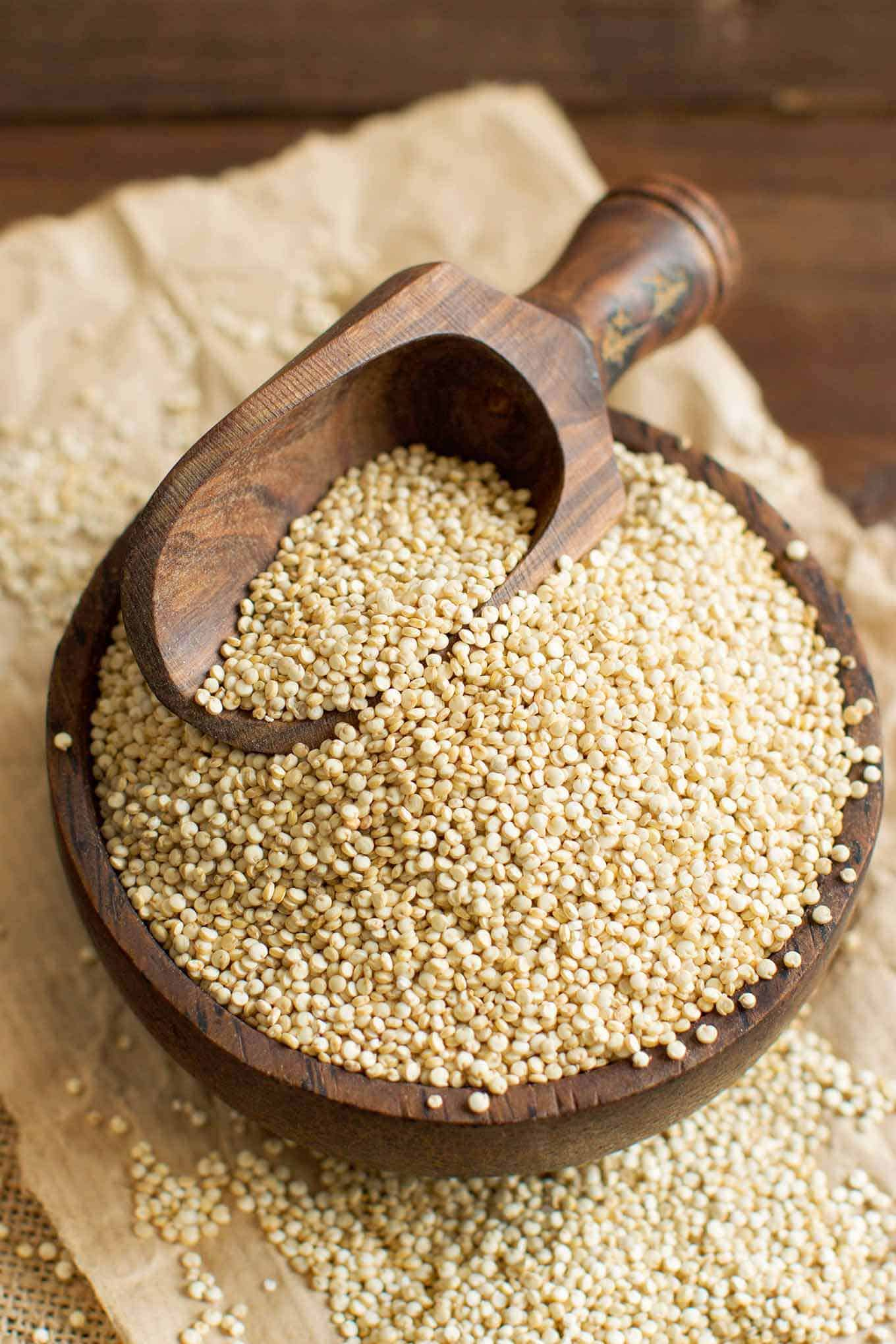 Raw quinoa in a wooden bowl with a measuring scoop.
