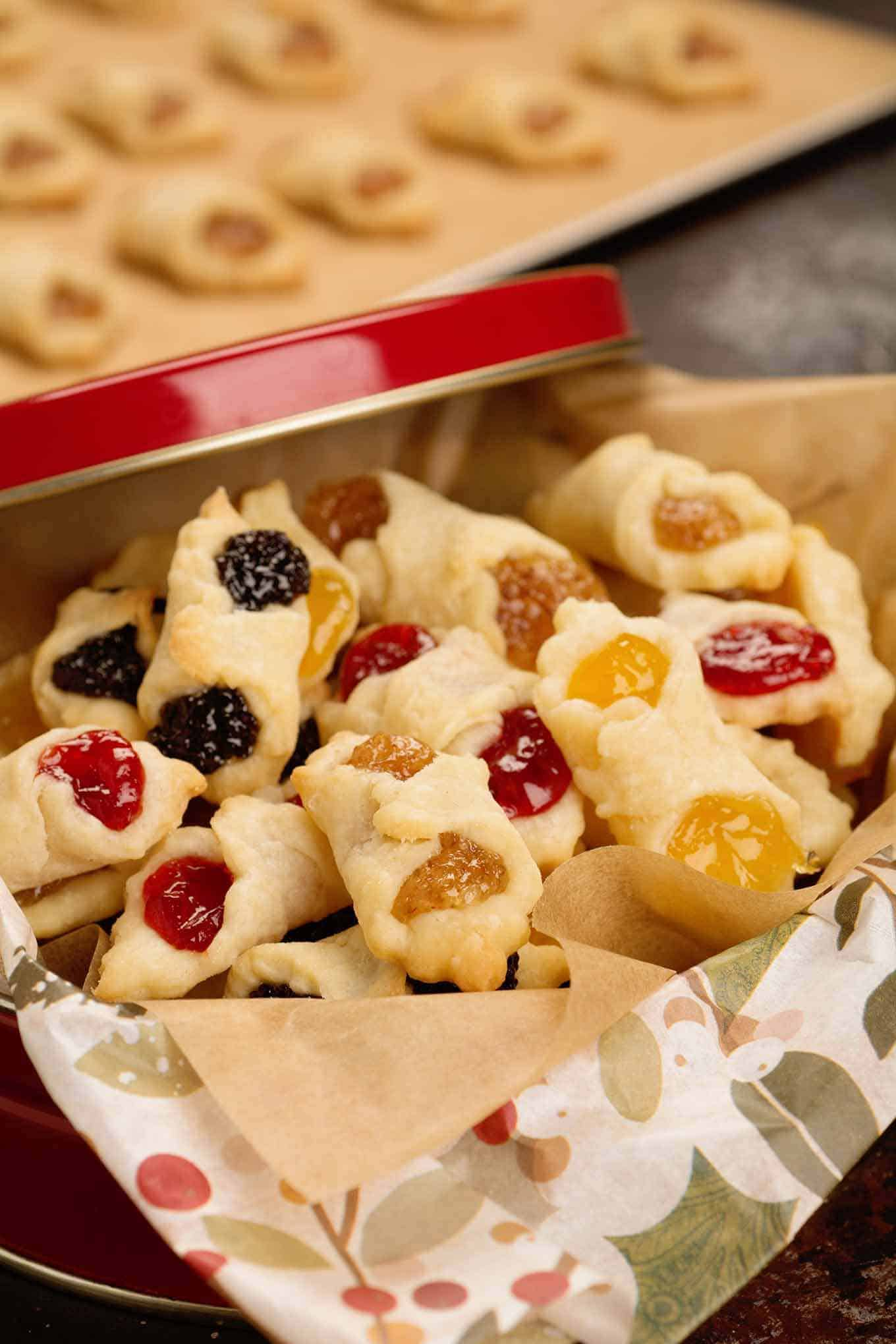 Open Christmas cookie tin lined with tissue and filled with an assortment of kiffles.