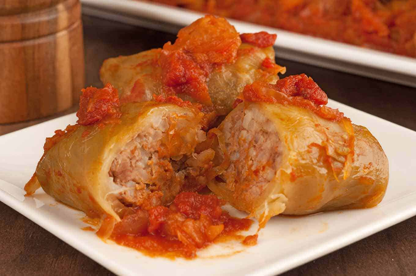 Hungarian stuffed cabbage roll cut in half, topped with sauce