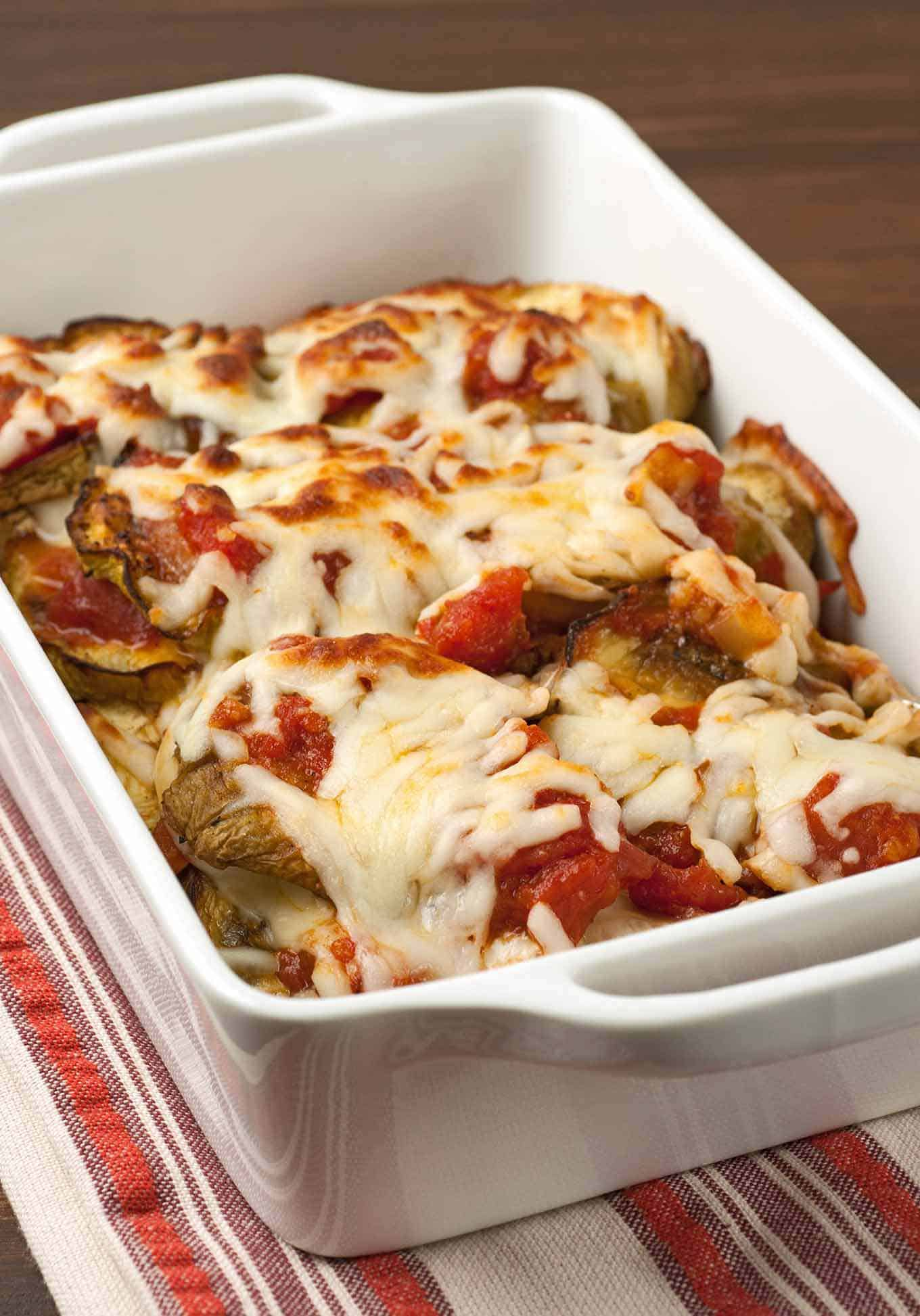 A casserole dish filled with roasted eggplant topped with marinara and melted mozzarella.