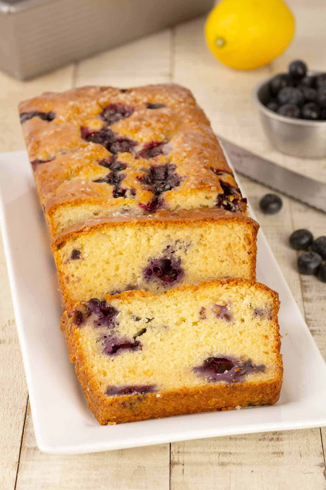 A serving plate of lemon blueberry loaf cake with slices off the end to show its interior texture.