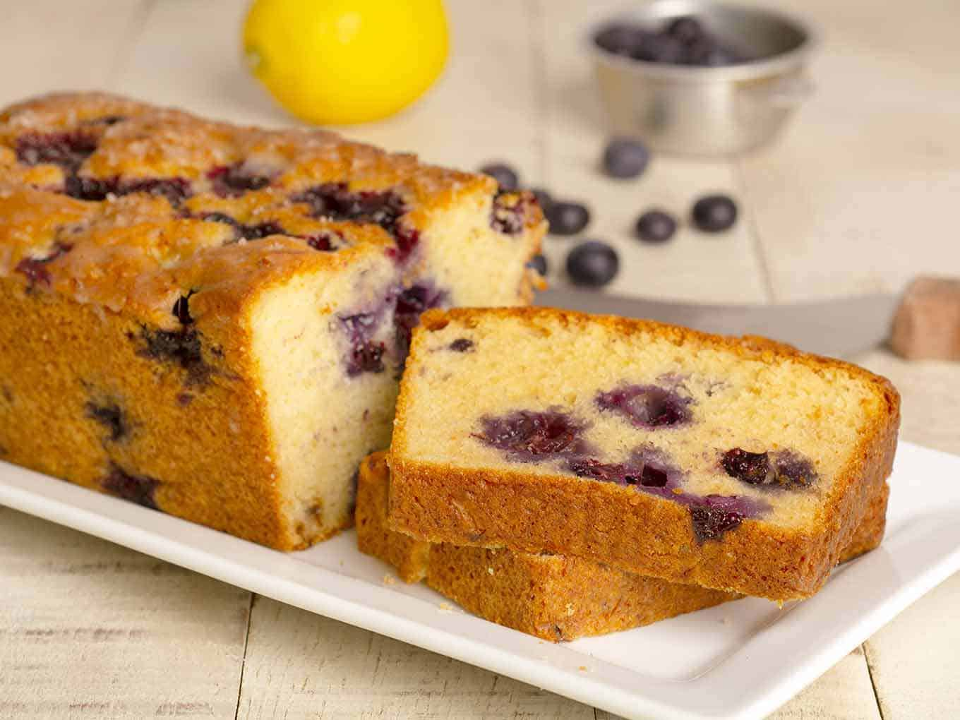 Slices of lemon blueberry cake on a serving plate with fresh ingredients in the background.