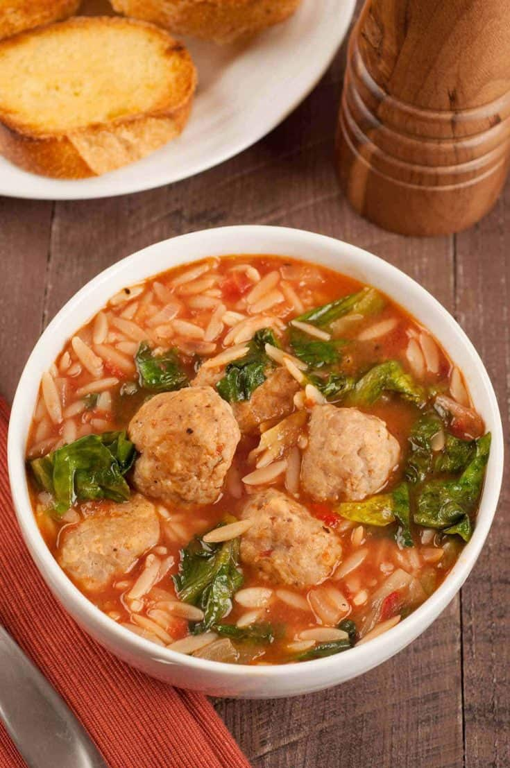 This hearty, one-dish dinner soup recipe combines bite-sized garlic and parmesan meatballs with orzo, diced tomatoes, and fresh escarole. #meatballsoup #escarolesoup #dinnersoup #meatballs #escarole