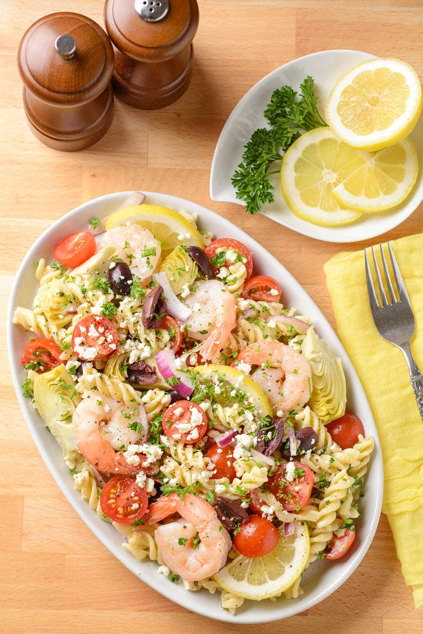 A plated serving of shrimp and pasta salad topped with feta cheese, extra lemon on the side.