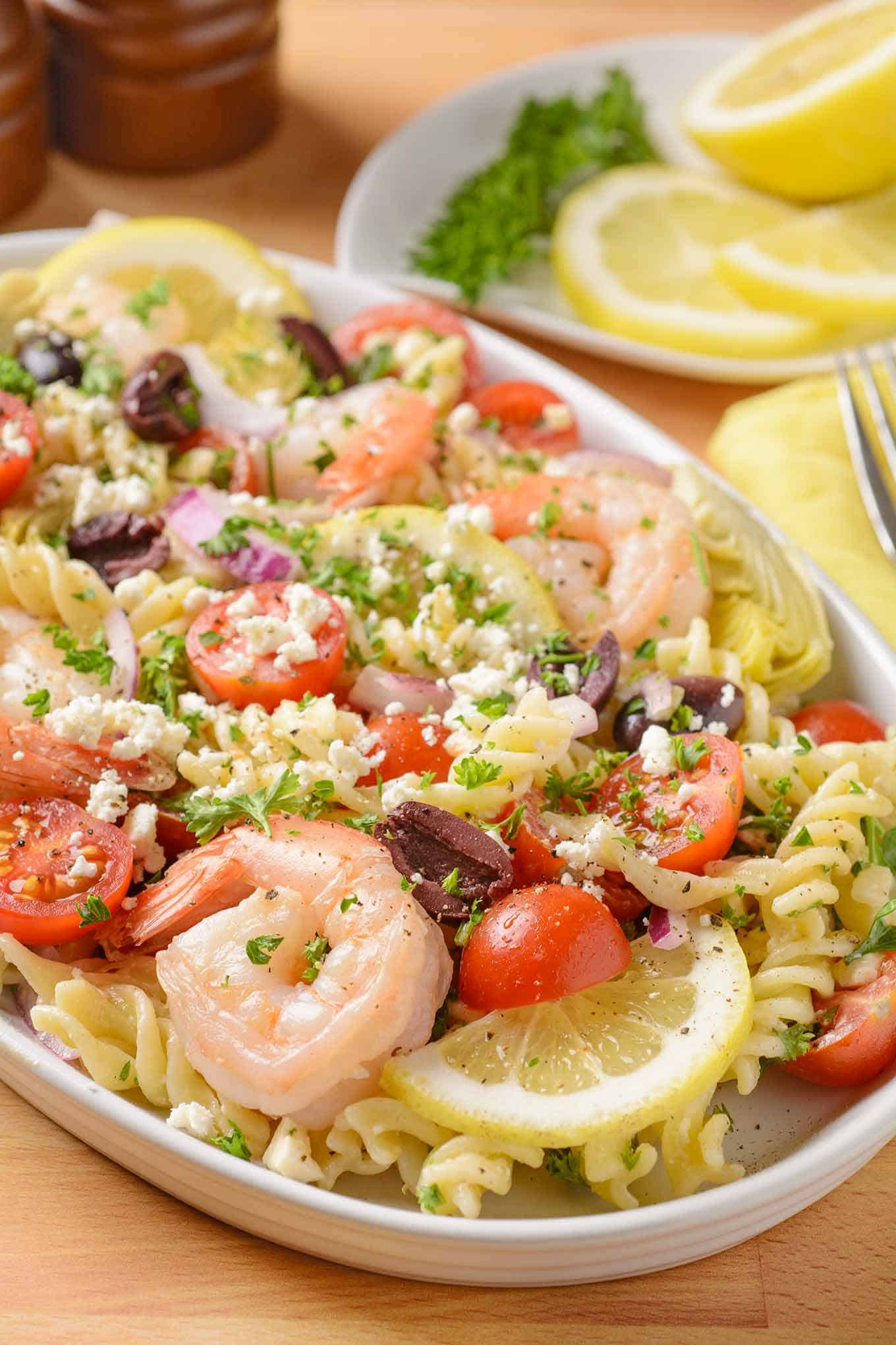 Rotini pasta salad with shrimp, artichoke hearts, Kalamata olives, cherry tomatoes, lemon, and feta cheese.