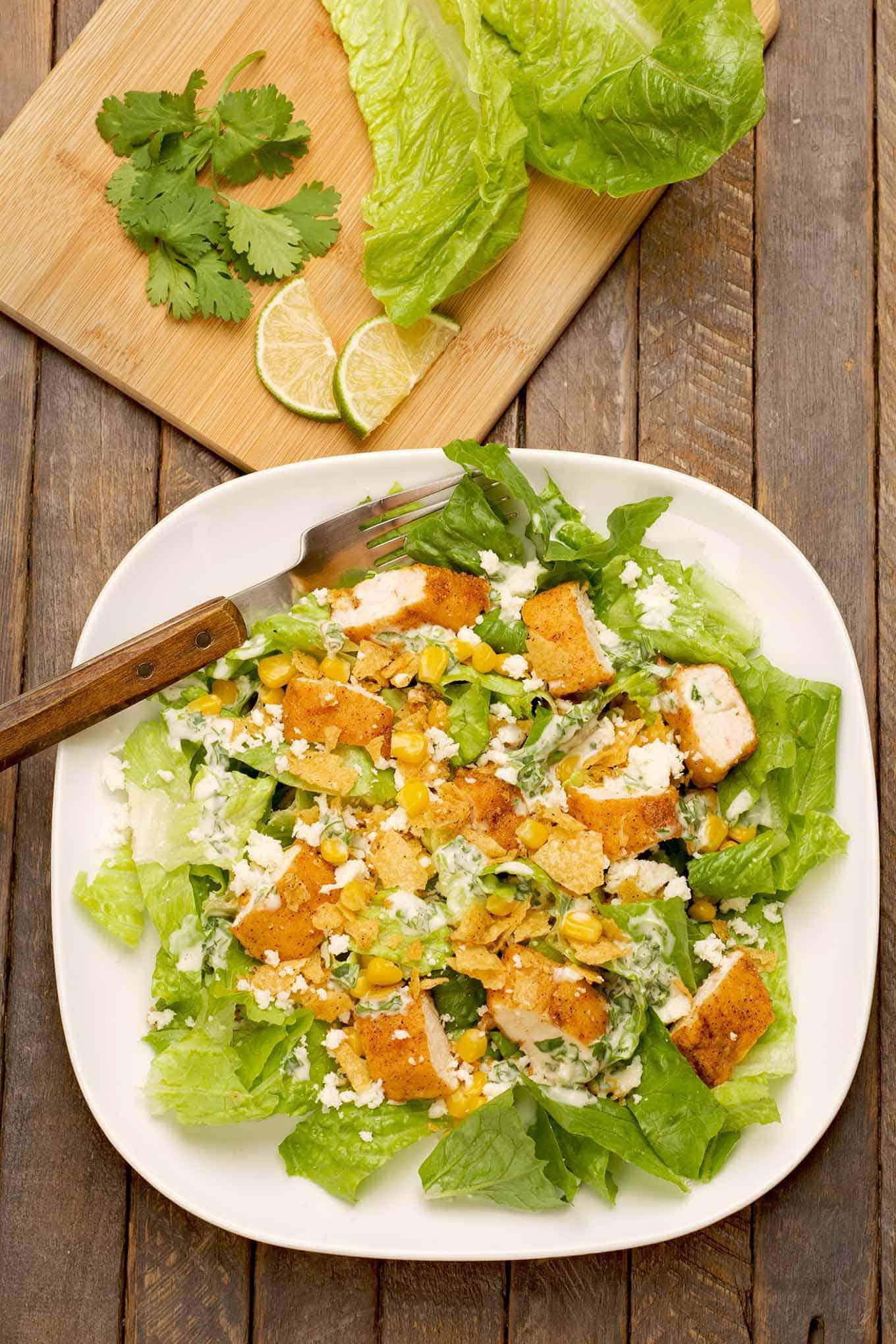 Mexican Caesar salad on a plate with some of the ingredients on a cutting board in the background.