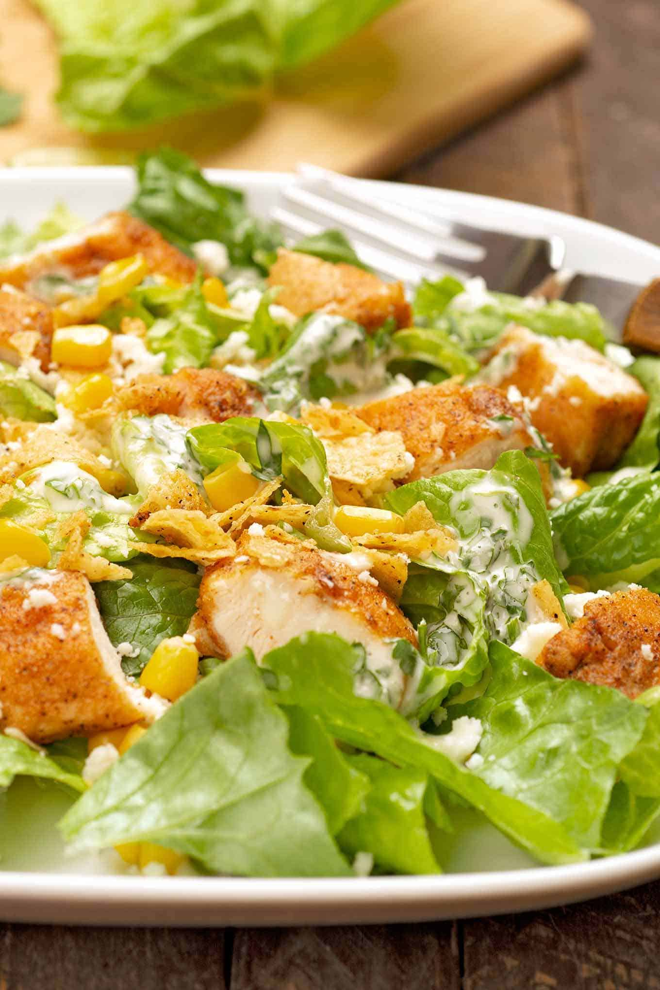 A serving of Caesar salad topped with breaded chicken, corn, cotija cheese, and tortilla chips.