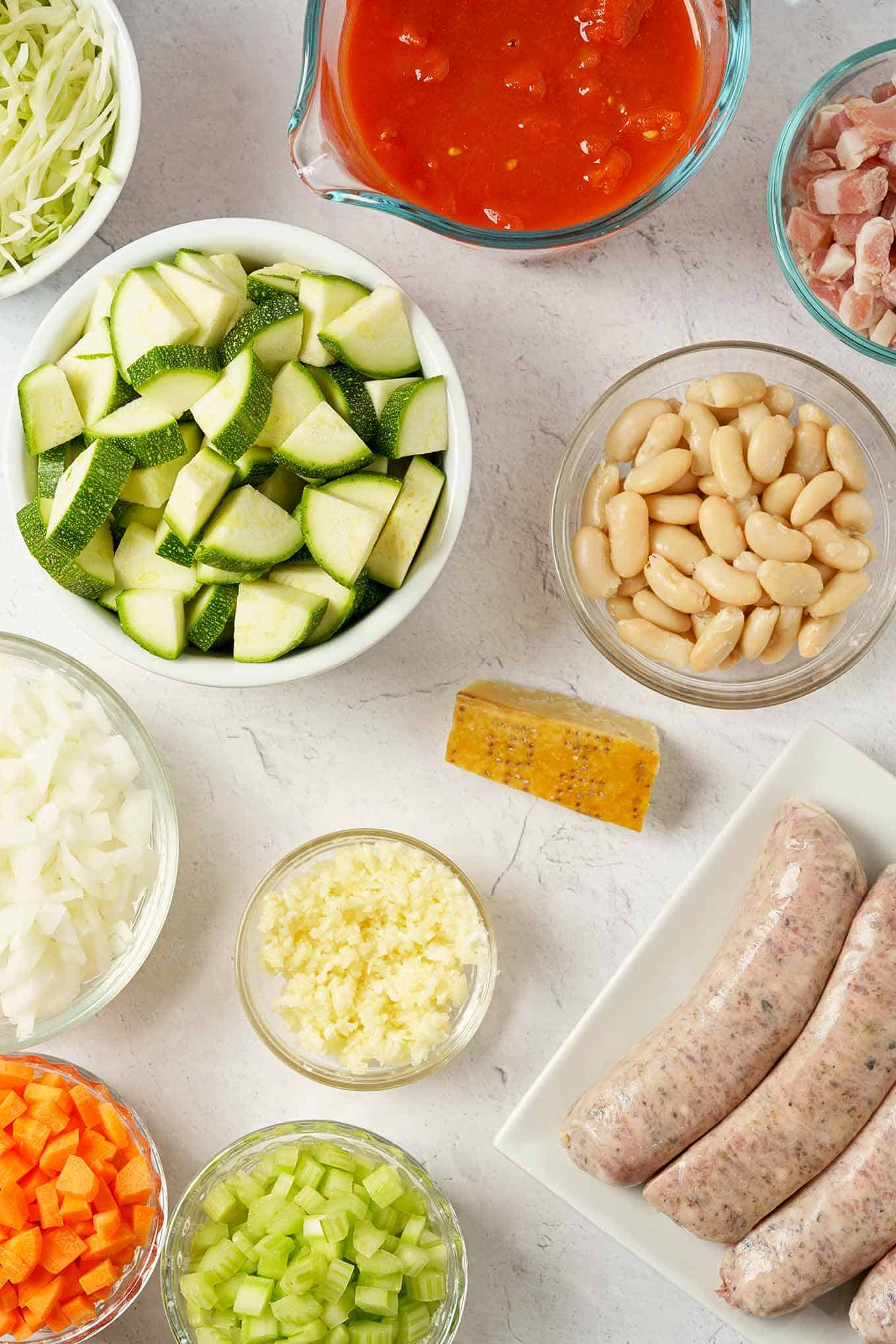 Prep dishes with minestrone soup ingredients including Italian sausage, zucchini, cannellini beans, and pancetta.