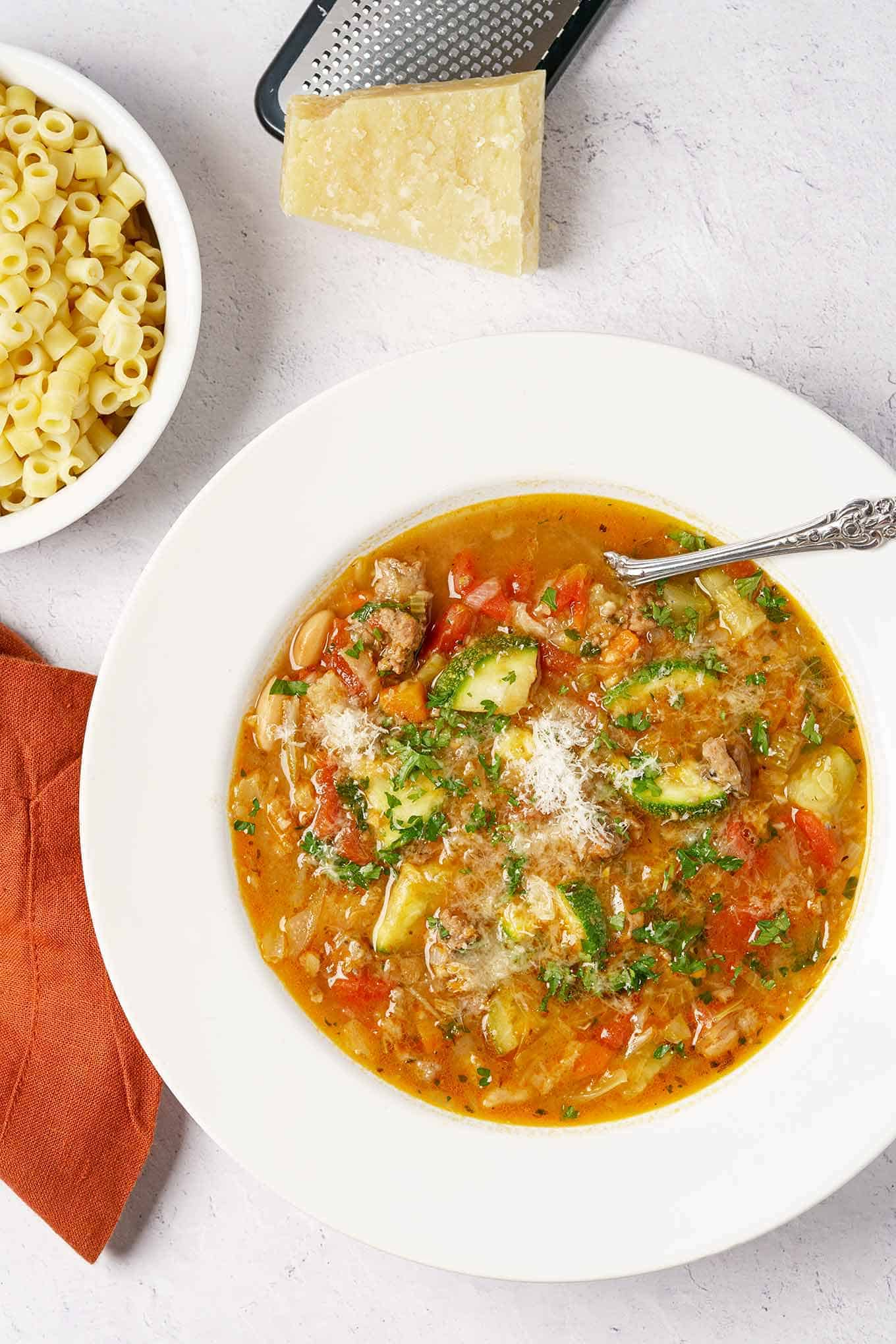 Bowl of homemade minestrone soup with ditalini and Parmesan cheese wedge on the side.