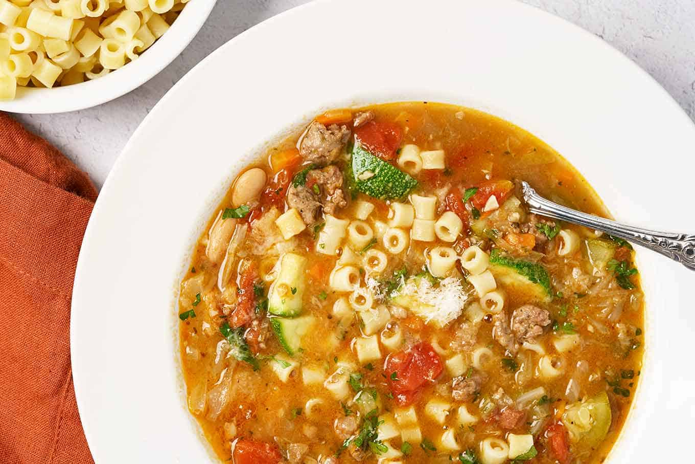 Bowl of minestrone soup with ditalini pasta added and grated Parmigiano-Reggiano cheese on top.