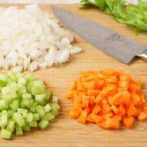 Mirepoix ingredients on a wooden cutting board: diced onion, carrots, and celery.