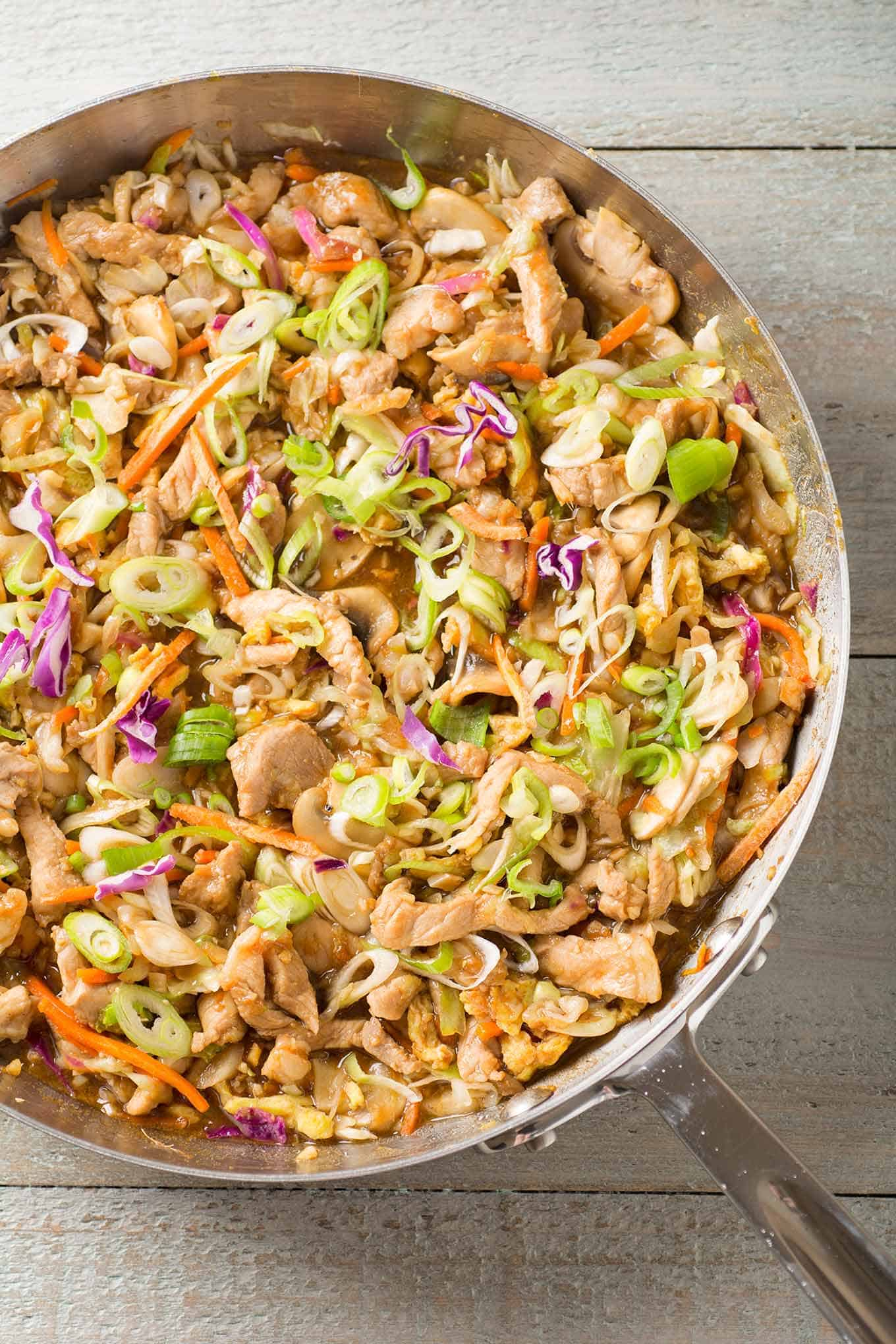 Moo Shu Pork in a frying pan made with stir-fried strips of pork, scallions, cabbage, and carrots.