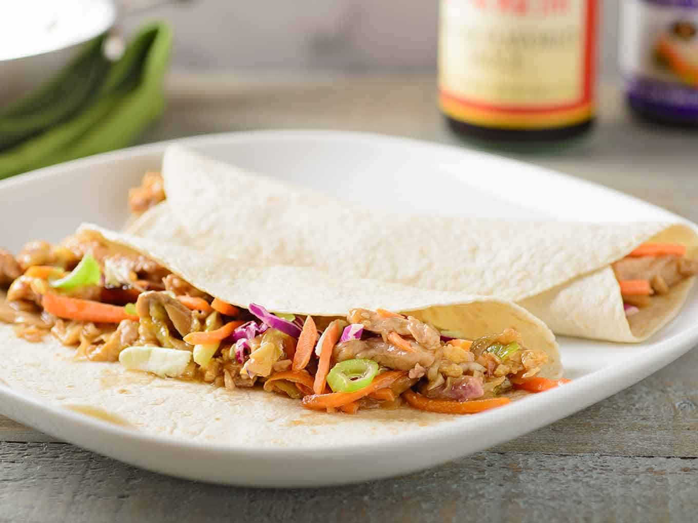 Two flour tortillas filled with Moo Shu Pork on a serving plate, one is partially open to show the ingredients.