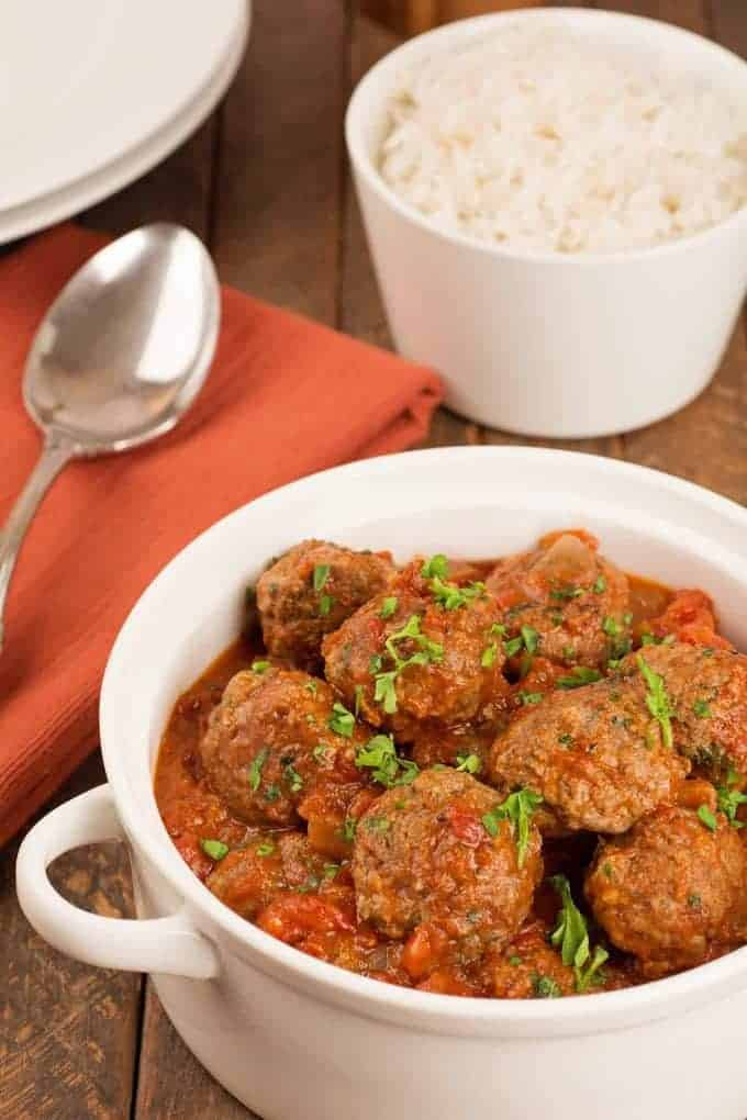 Moroccan lamb meatballs in a serving dish, serving spoon, and a side dish of white rice