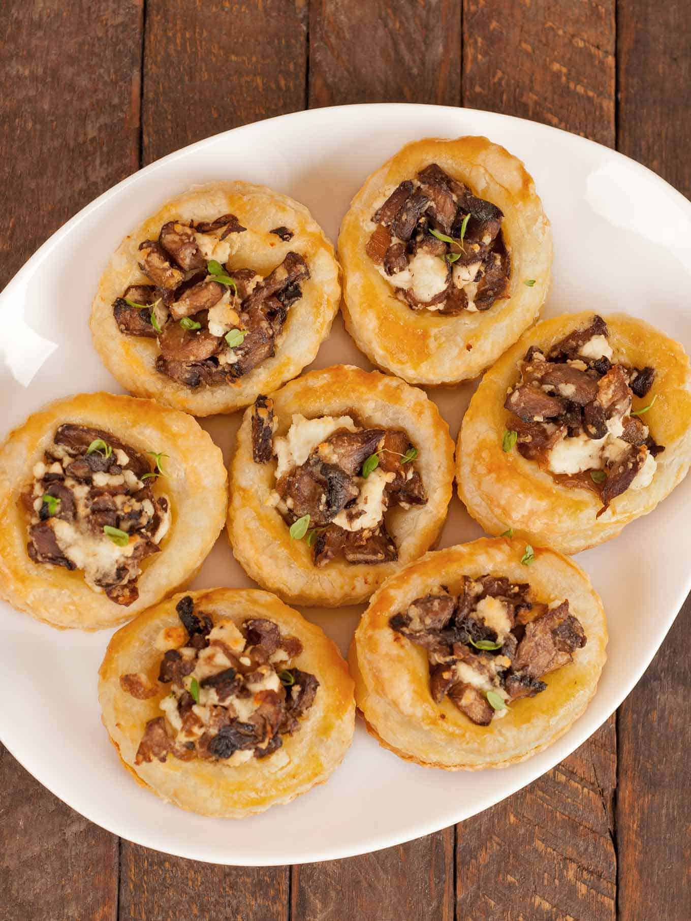 A serving plate with puff pastry cups filled with sautéed mushrooms and crumbled goat cheese.