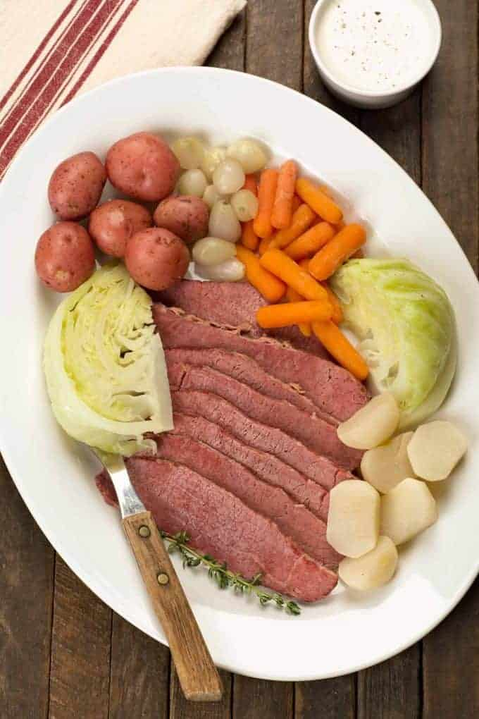 Sliced corned beef, cabbage wedges, carrots, turnips, pearl onions and red potatoes on a serving platter.