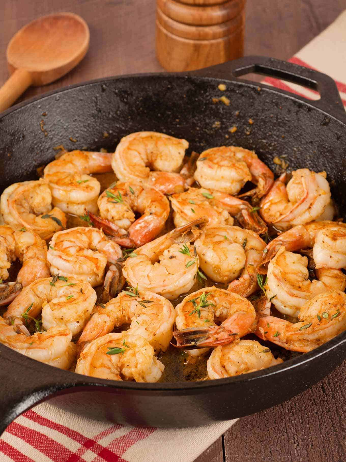 Sautéed shrimp in cast iron skillet seasoned with Old Bay Seasoning and garnished with fresh thyme leaves.