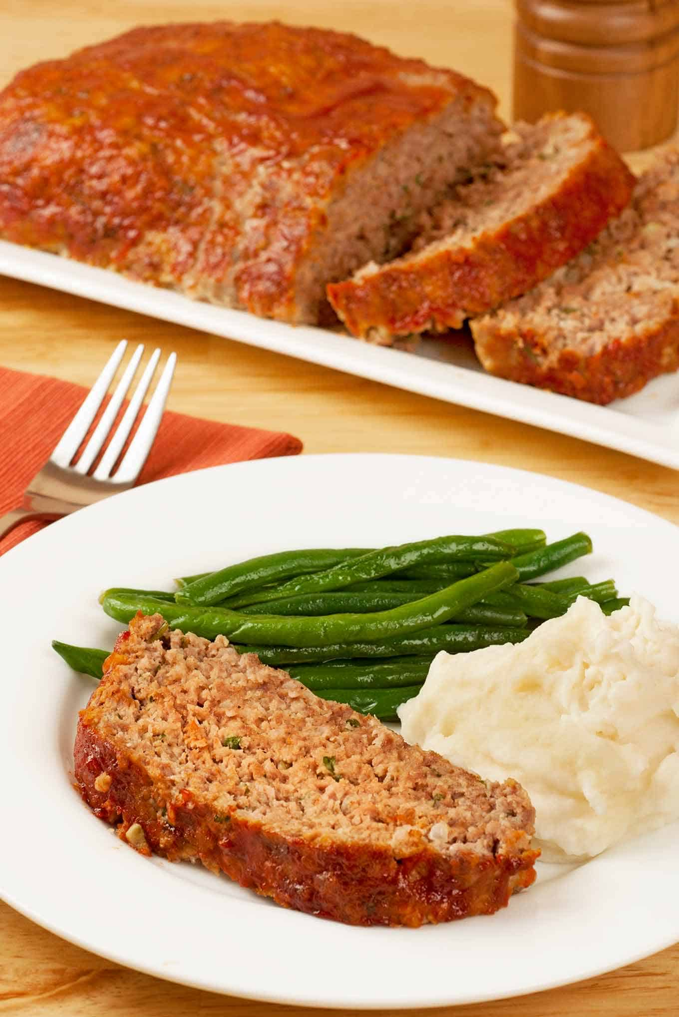 Slice of meatloaf on a plate with mashed potatoes and green beans and serving platter of meatloaf in the background.