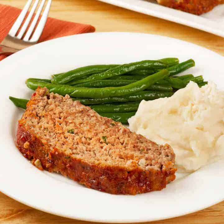 Slice of meatloaf on a plate with green beans and mashed potatoes.