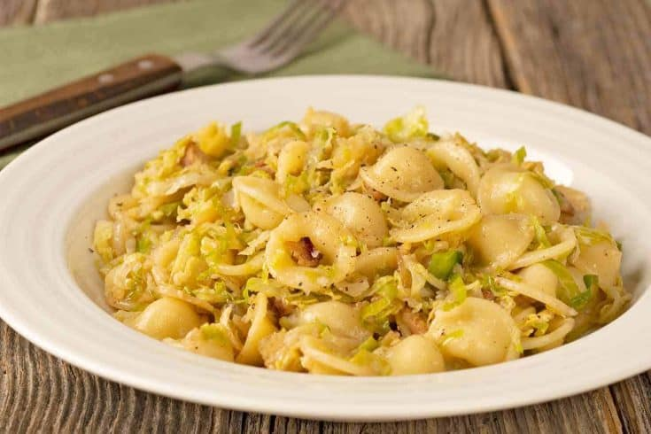 This deliciously garlicky combination of caramelized onion, shredded Brussels sprouts and pasta makes a satisfying dinner that's fast and easy to prepare. #pasta #brusselssprouts #bacon