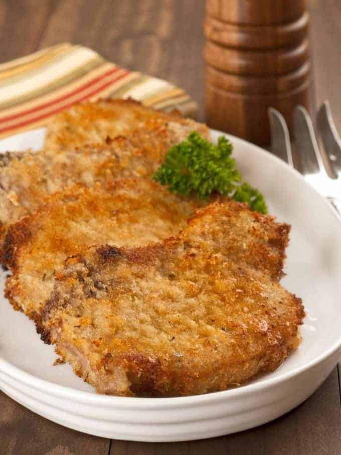 Oven-fried parmesan pork chops on a serving plate
