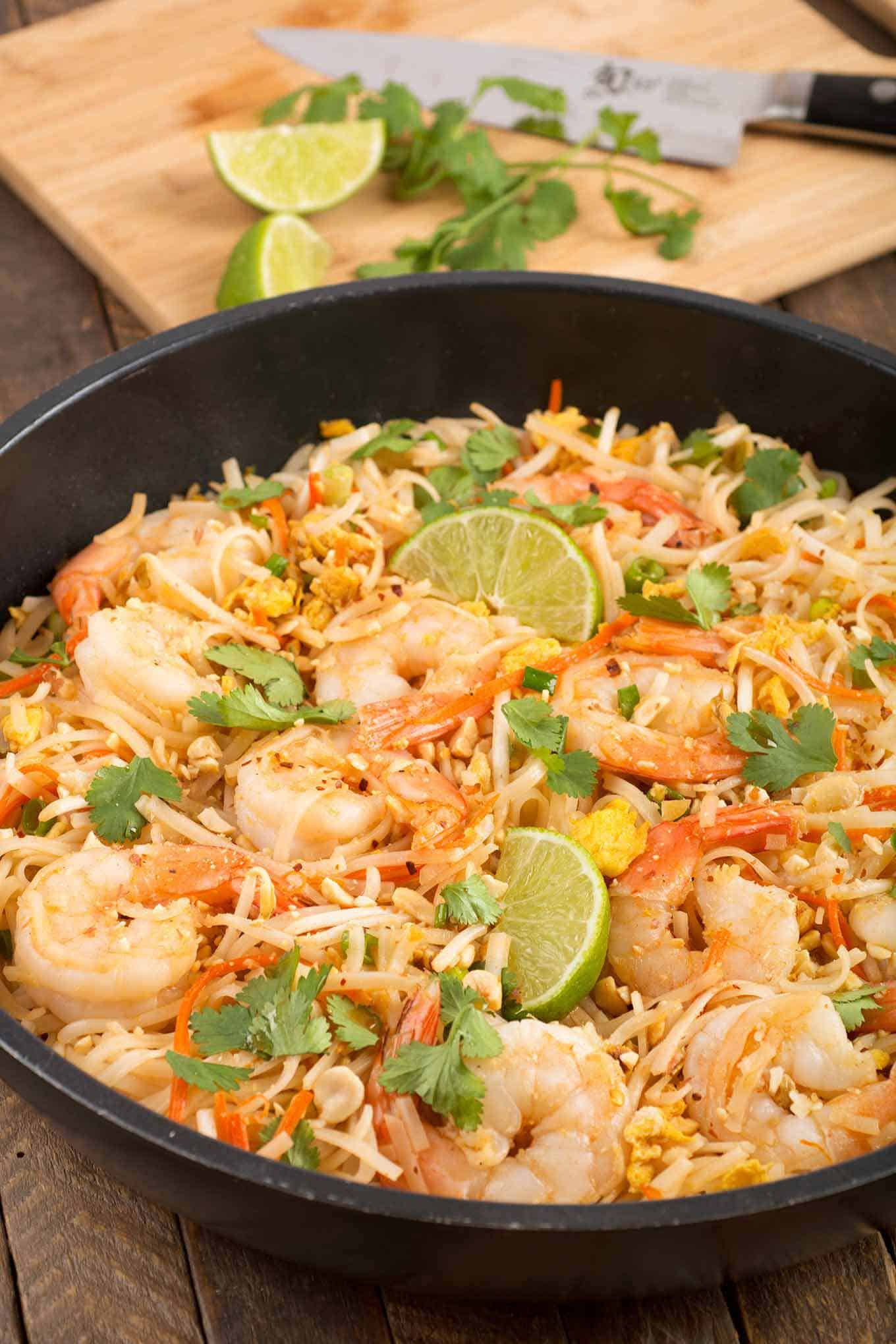 Shrimp Pad Thai in a frying pan garnished with lime wedges and cilantro, cutting board in the background.