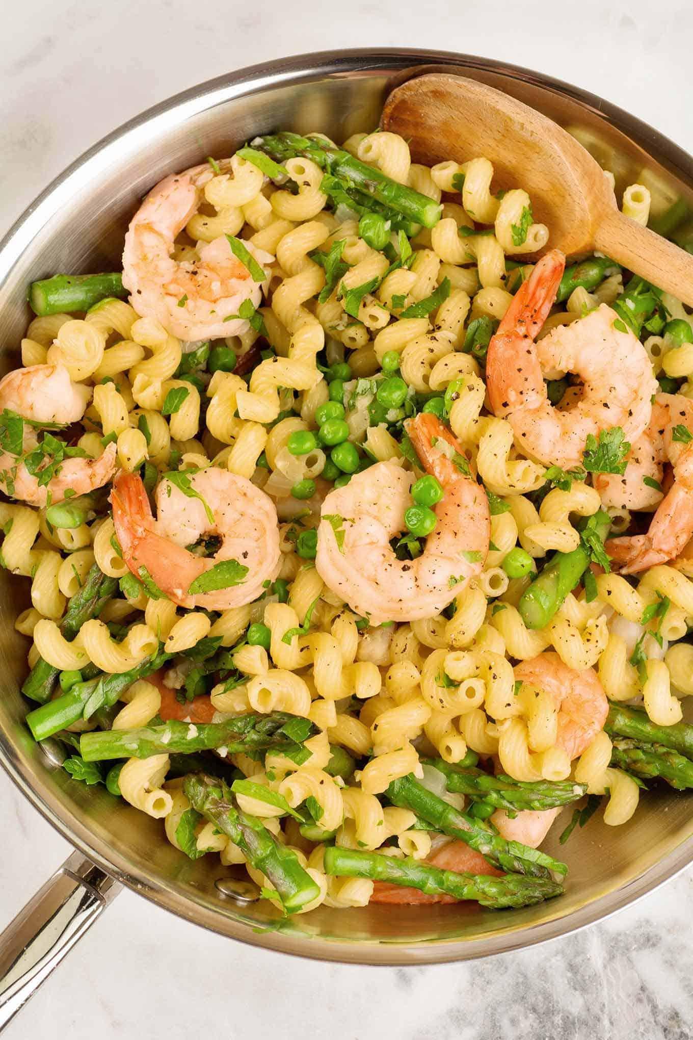 Sauté pan filled with corkscrew pasta, shrimp, asparagus, and peas