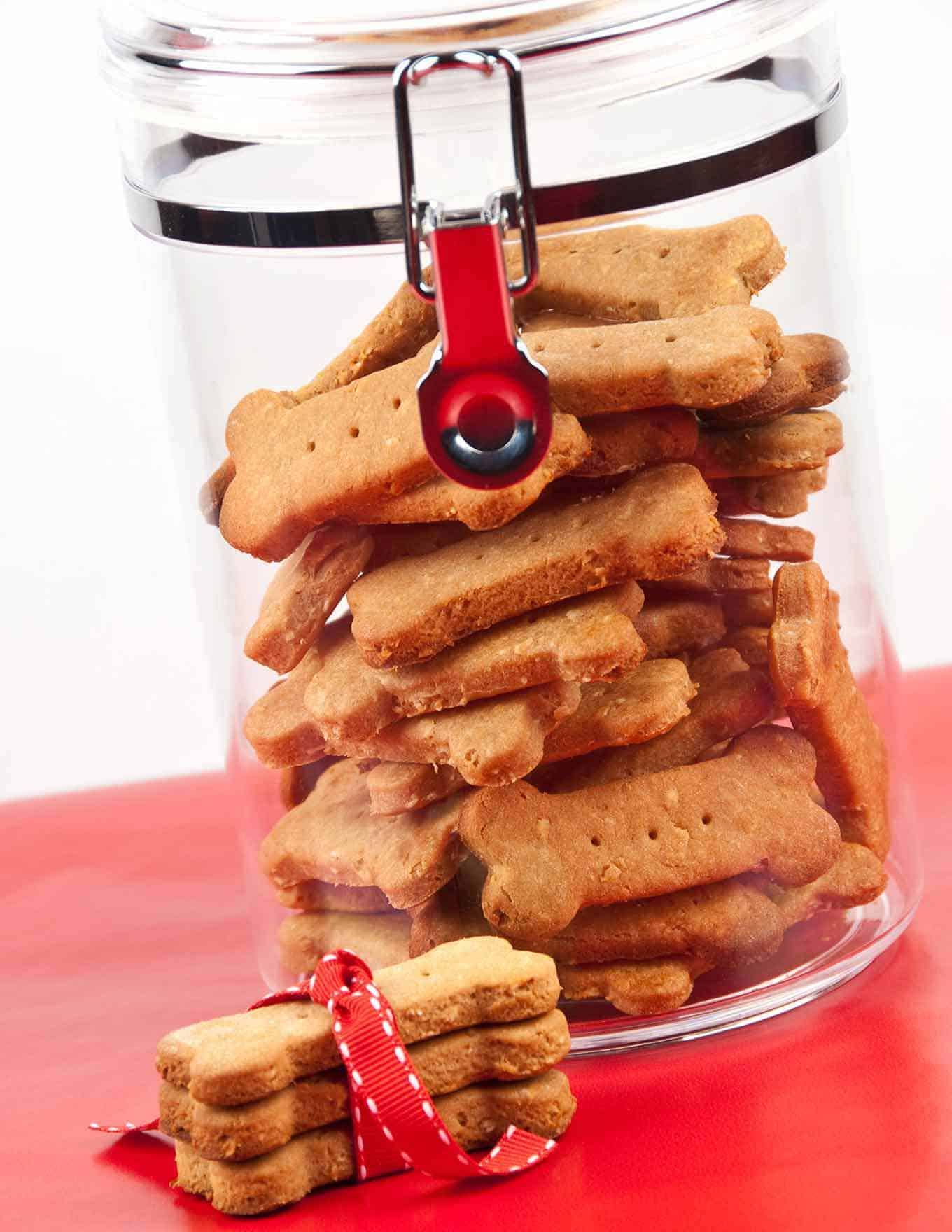 Clear canister with bone-shaped peanut butter dog biscuits inside.