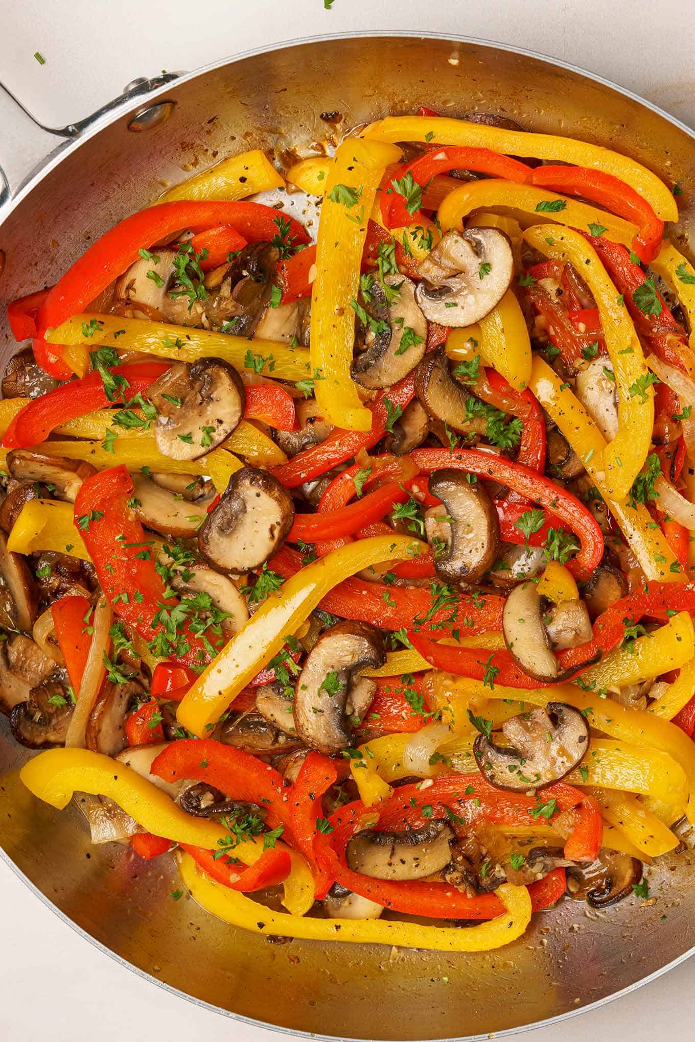 Sautéed bell peppers, mushrooms, and onions in a frying pan.