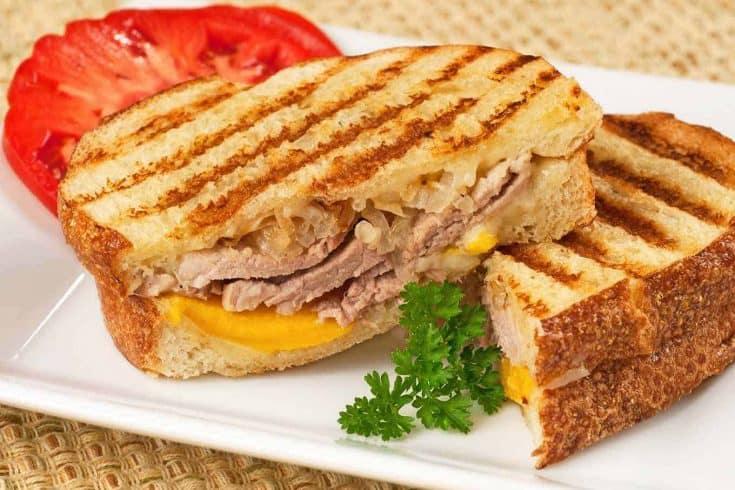 This sweet and savory roast pork panini sandwich is made with sourdough bread, sliced peaches, sautéed onion, and sharp cheddar cheese. #porkpanini #paninisandwich #panini #roastporktenderloin