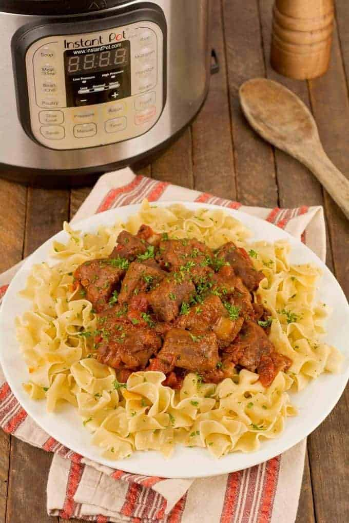 Serving plate of egg noodles topped with beef goulash with an Instant Pot  in the background