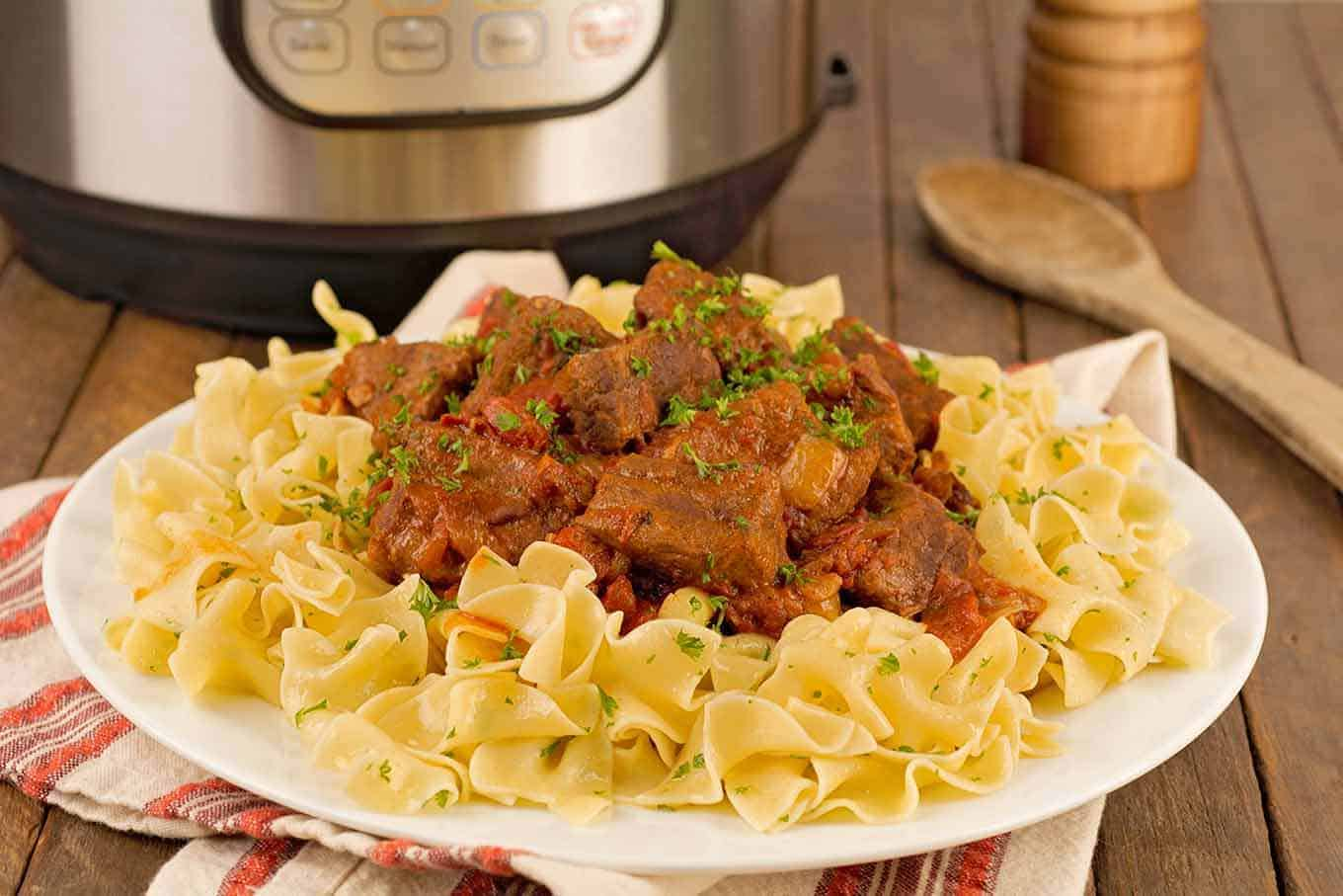 Plate of egg noodles and beef goulash garnished with chopped parsley