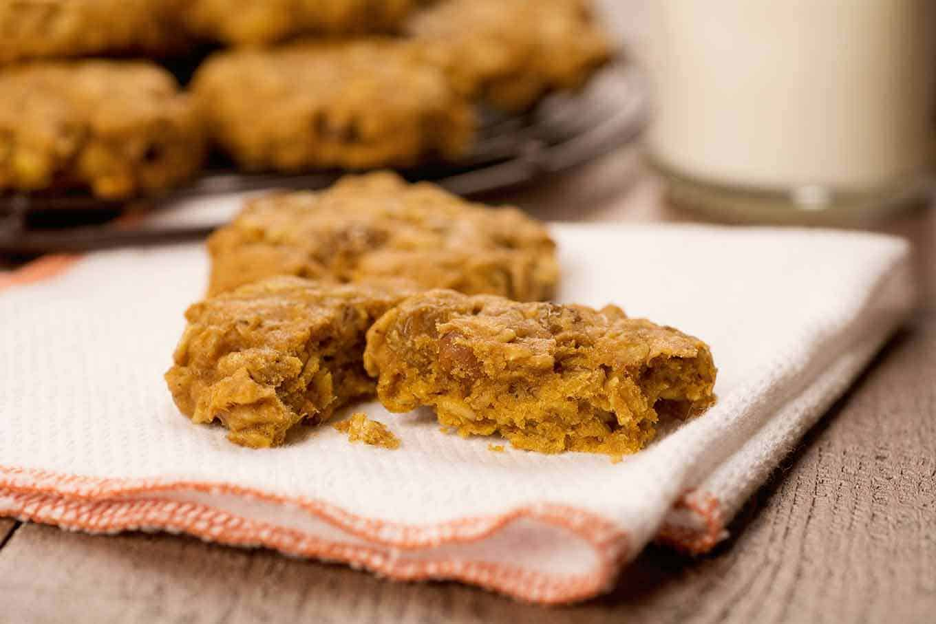 A pumpkin oatmeal cookie on a cloth napkin, broken in half with a glass of milk in the background.