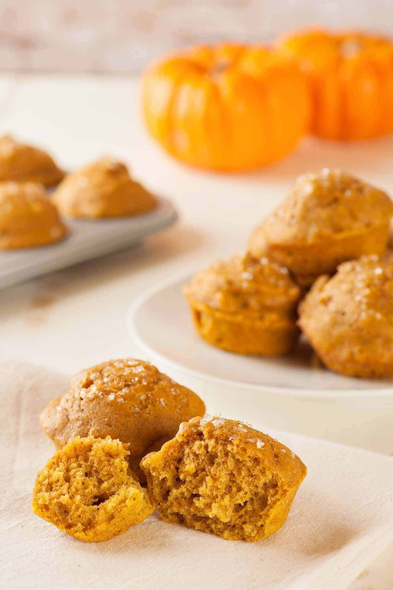 Single pumpkin muffin on a napkin with a serving plate of whole muffins in the background.