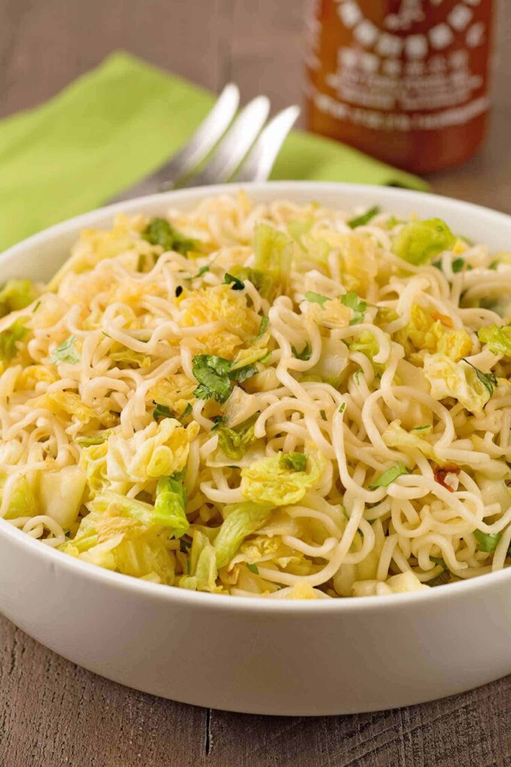 This satisfying ramen noodle side dish is made with sautéed savoy cabbage and flavored with a spicy, sriracha-garlic butter, scallions and cilantro. #ramennoodles #ramensidedish #ramen #cabbagenoodles