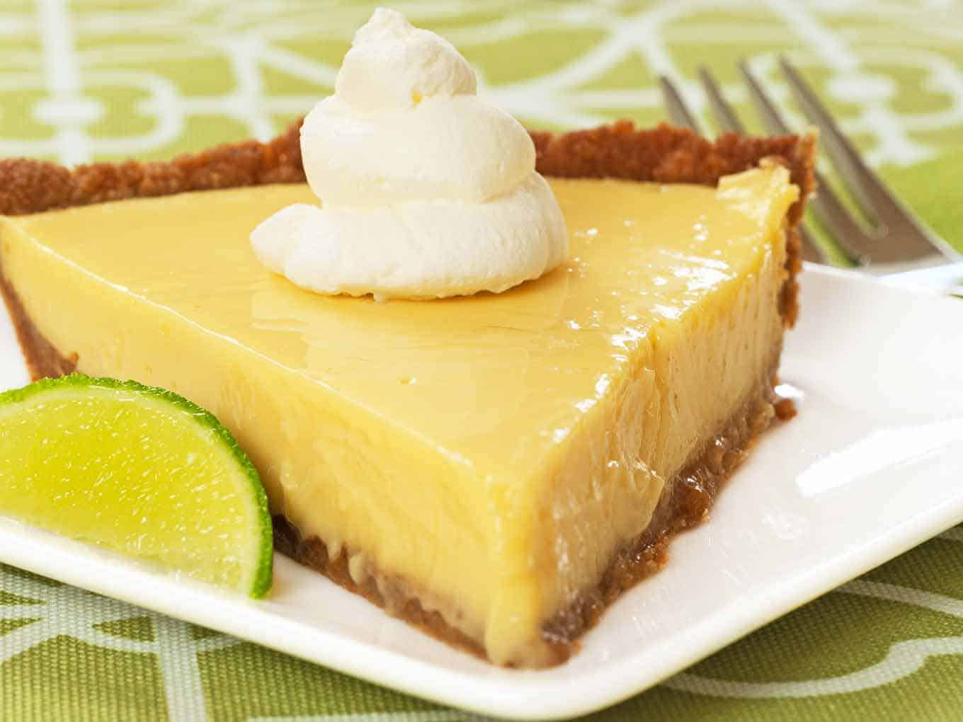 A serving of key lime pie topped with whipped cream and garnished with a lime wedge.