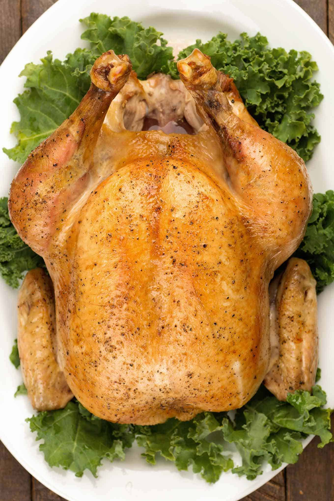 Perfectly browned roast capon on a serving platter garnished with raw kale.