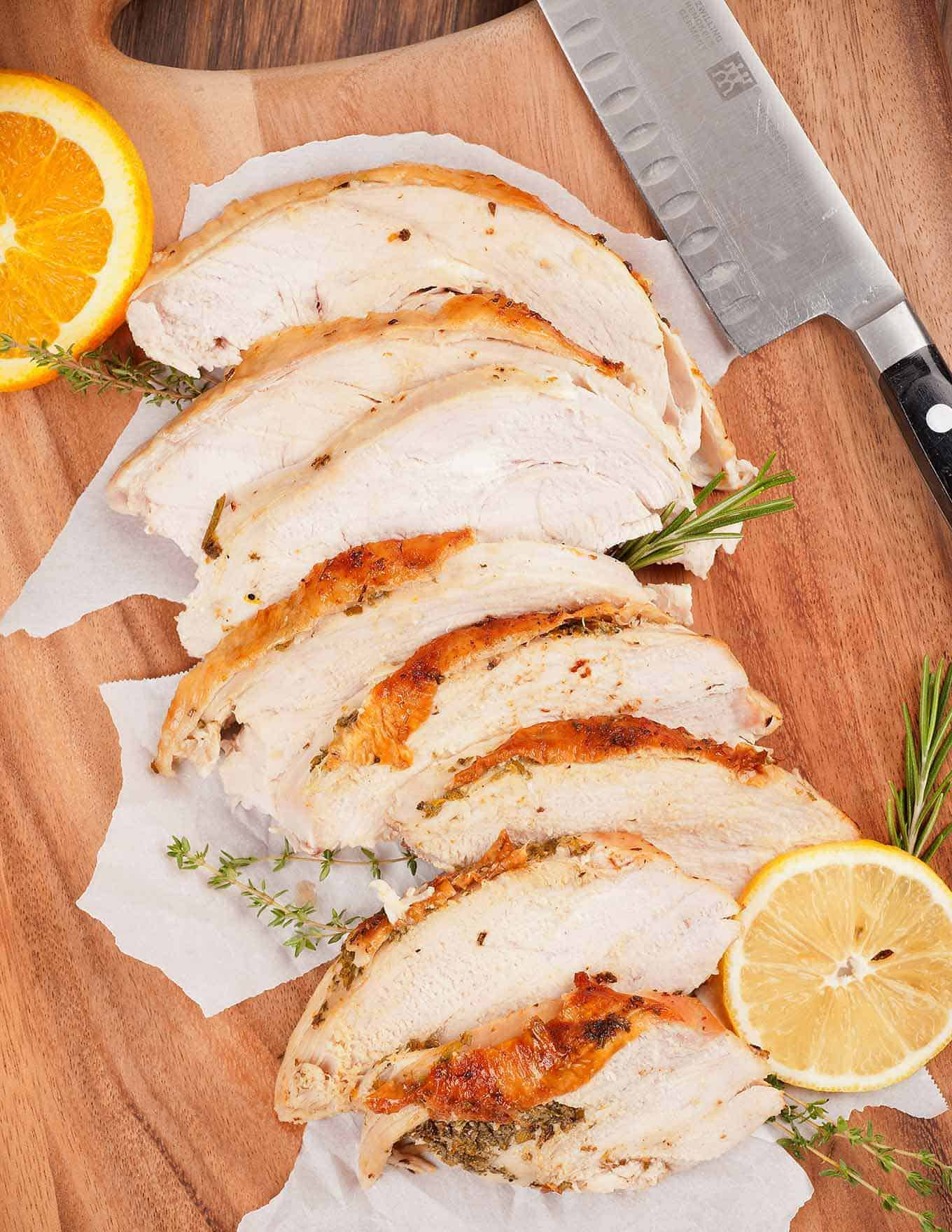 Slices of roasted turkey breast on a cutting board with carving knife and lemon and orange rounds.