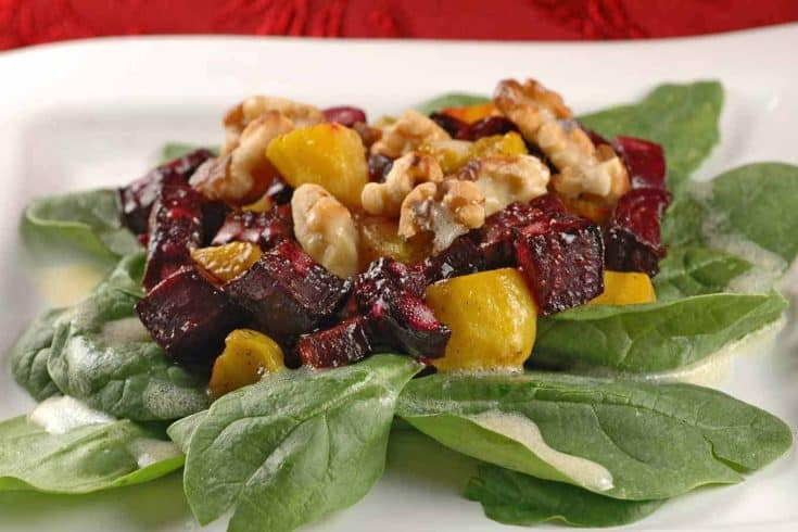 This healthy, composed salad is a perfect starter and includes roasted beets, toasted walnuts, fresh spinach, and a creamy, orange dressing. #beets #beetsalad #roastedbeetsalad