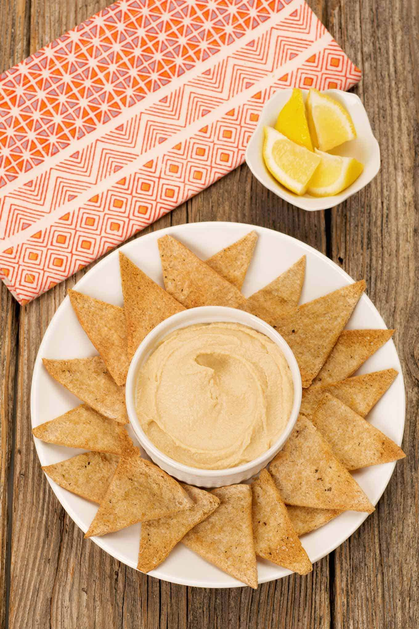 Serving plate with a bowl of hummus in the center, pita triangles surrounding it and lemon wedges in a small bowl on the side.