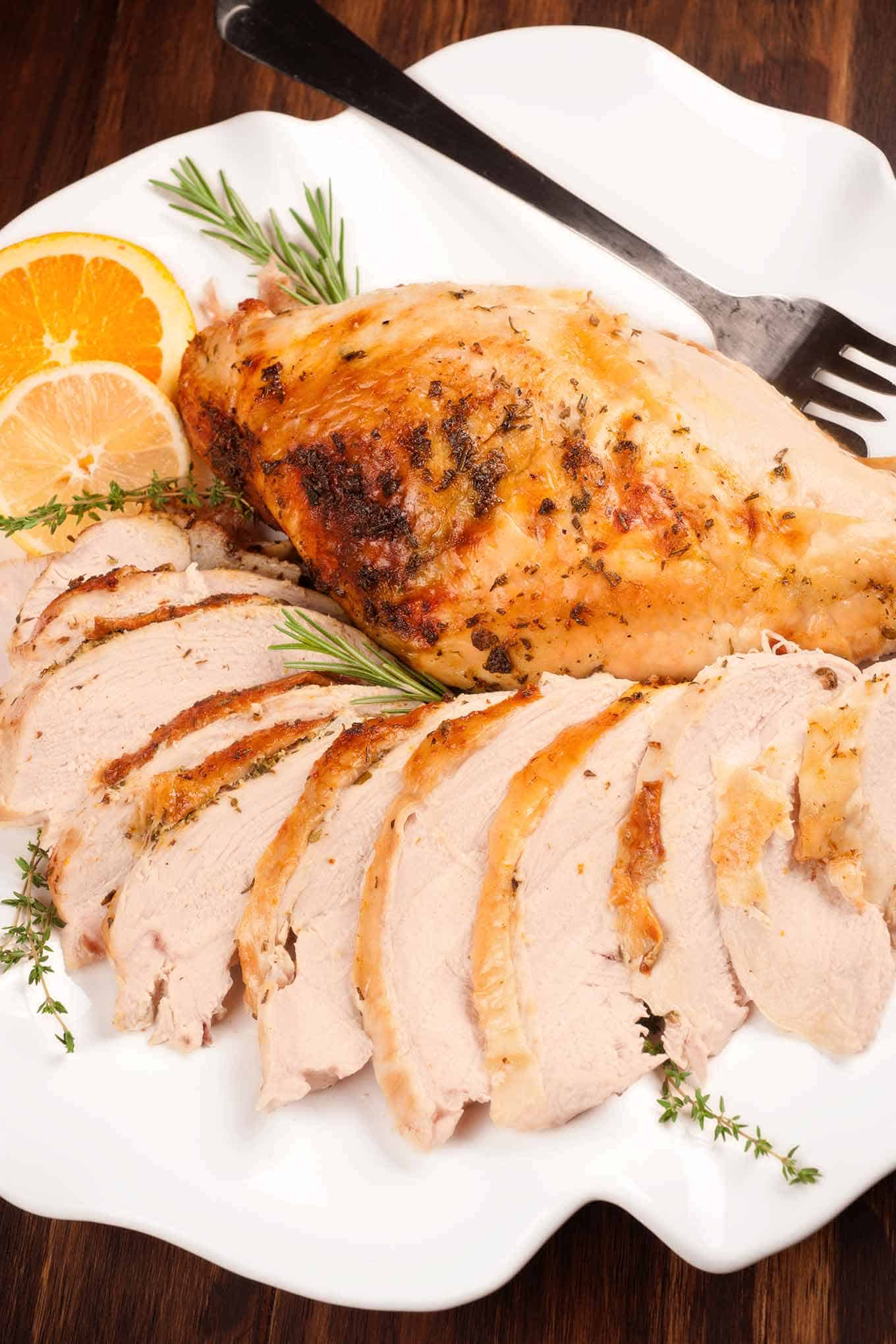 Slices of roasted turkey breast and unsliced turkey on a serving platter.
