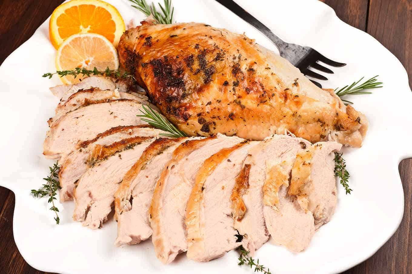 Platter of roasted turkey breast with citrus herb butter, serving fork and rosemary and thyme garnish